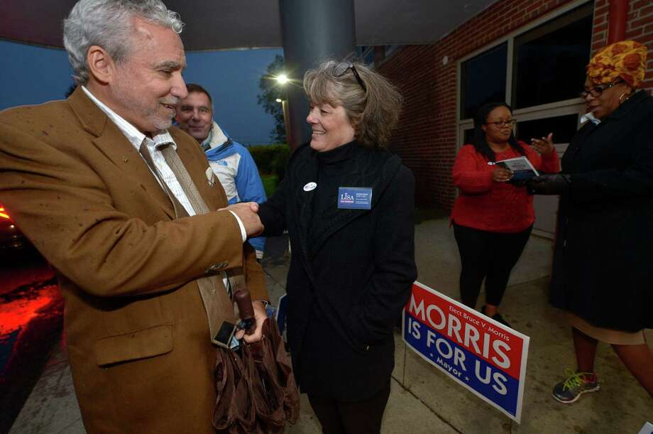 Johnny Cardamone greets Independent petition candidate for mayor Lisa Brinton as she campaigns outside Nathan Hale Middle School Tuesday, Nov. 8, in Norwalk. Photo: Erik Trautmann / Hearst Connecticut Media / Norwalk Hour