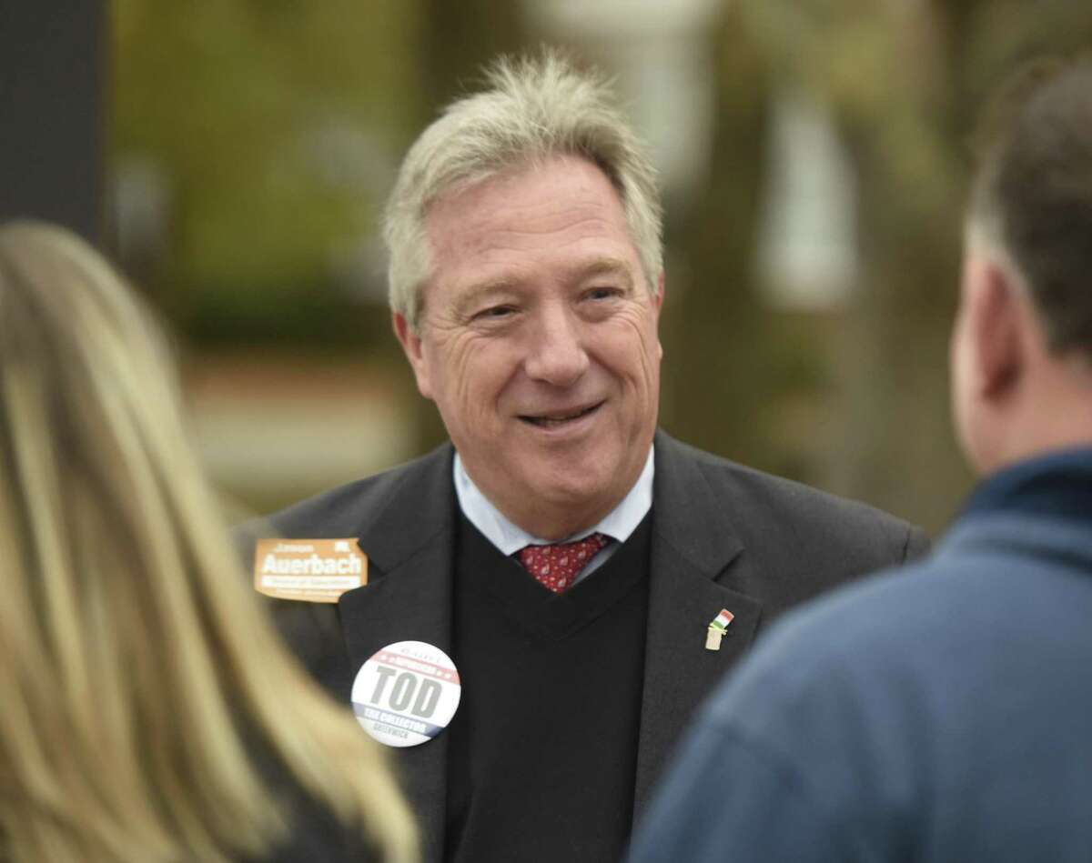 Incumbent Republican Tax Collector Tod Laudonia chats outside North Mianus School, the District 12 polling center, on Election Day in Greenwich, Conn. Tuesday, Nov. 7, 2017.