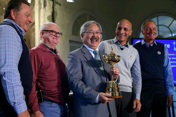 Mayor Ed Lee carries the Ryder Cup to the stage after PGA of America officials announce that the Olympic Club will host the 2028 PGA Championship and the Ryder Cup in 2032, in San Francisco, Calif. on Wednesday, Nov. 8, 2017. Standing with the mayor is, from left, PGA of America president Paul Levy, Olympic Club president Dan Dillon, Pete Bevacqua, PGA of America CEO and Kerry Haigh, the chief championships officer for PGA of America.