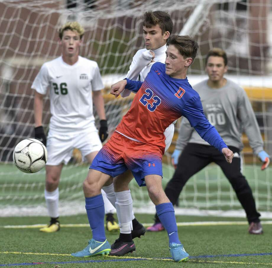 Danbury's Riley Moore (23) was in position to get the ball, on a corner kick, in front of New Milford's Alexander Michalek (9) in the boys State Class LL Soccer game between Danbury and New Milford high schools, Wednesday afternoon at New Milford High School, in New Milford, Conn, November 8, 2017. New Milford goalie Brandon Romero (00) and Sean Murphy (26) watch from the goal. Photo: H John Voorhees III / Hearst Connecticut Media / The News-Times