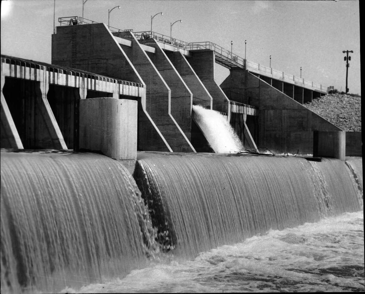 Water pours over San Jacinto Dam out of Lake Houston. Completed in 1955 on the San Jacinto River, the lake at capacity is 12,500 acres big and holds 52 billion gallons of water. The lake has developed into a playground as well as a reservoir for the city of Houston.