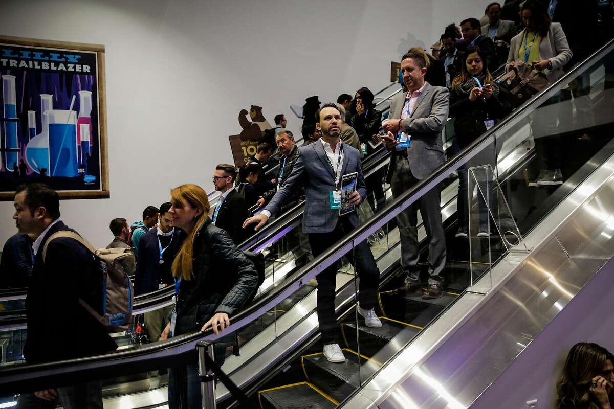 The chair of the dreamforce event Michael Peachey (center) rides the escalator into the Moscone center south in San Francisco, Calif., on Wednesday, Nov. 8, 2017.