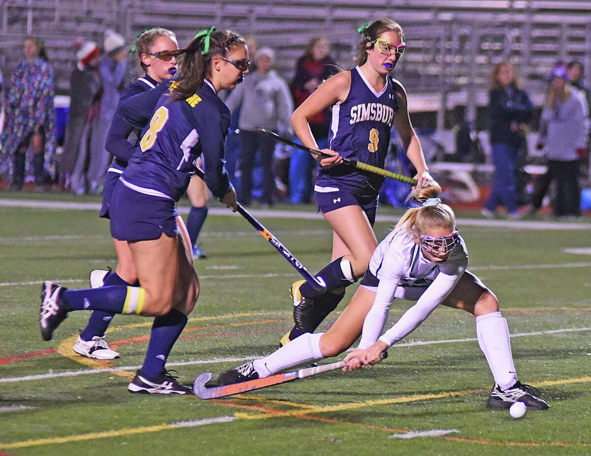 Norwalk's Tessa Albrecht gets low to fire off a shot before a trio of Simsbury defenders can step in during Wednesday's Class L playoff game.