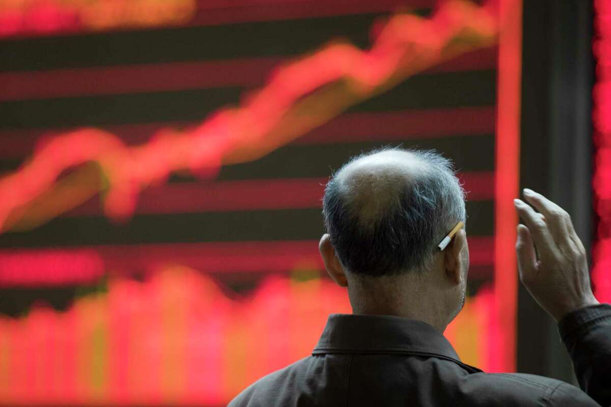 A man reaches for a cigarette tucked behind his ear at a stock brokerage in Beijing, China, Wednesday, Nov. 8, 2017. Asian stocks were mixed Wednesday after Wall Street declined as President Donald Trump delivered a new warning to North Korea in a speech to South Korean lawmakers. (AP Photo/Ng Han Guan)