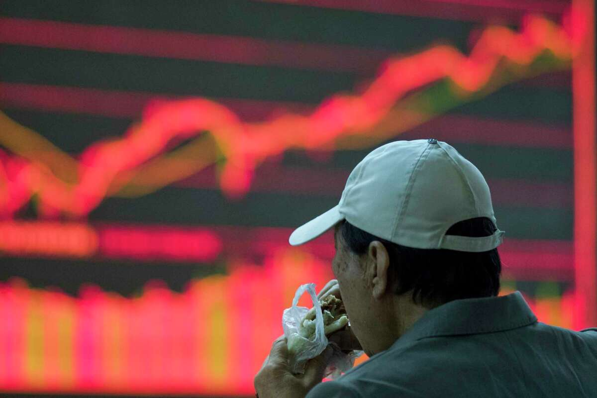 A man eats while monitoring stock prices at a brokerage in Beijing, China, Wednesday, Nov. 8, 2017. Asian stocks were mixed Wednesday after Wall Street declined as President Donald Trump delivered a new warning to North Korea in a speech to South Korean lawmakers. (AP Photo/Ng Han Guan)