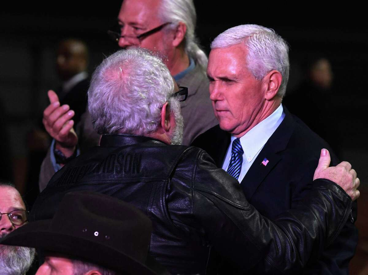 US Vice President Mike Pence (R) hugs Stephen Willeford during a 'Prayer Vigil Honoring Victims of the First Baptist Church Shooting' at the Floresville High School in Texas on November 8, 2017. A gunman wearing all black armed with an assault rifle opened fire on a small-town Texas church during Sunday morning services, on November 5, killing 26 people and wounding 20 more in the last mass shooting to shock the United States.