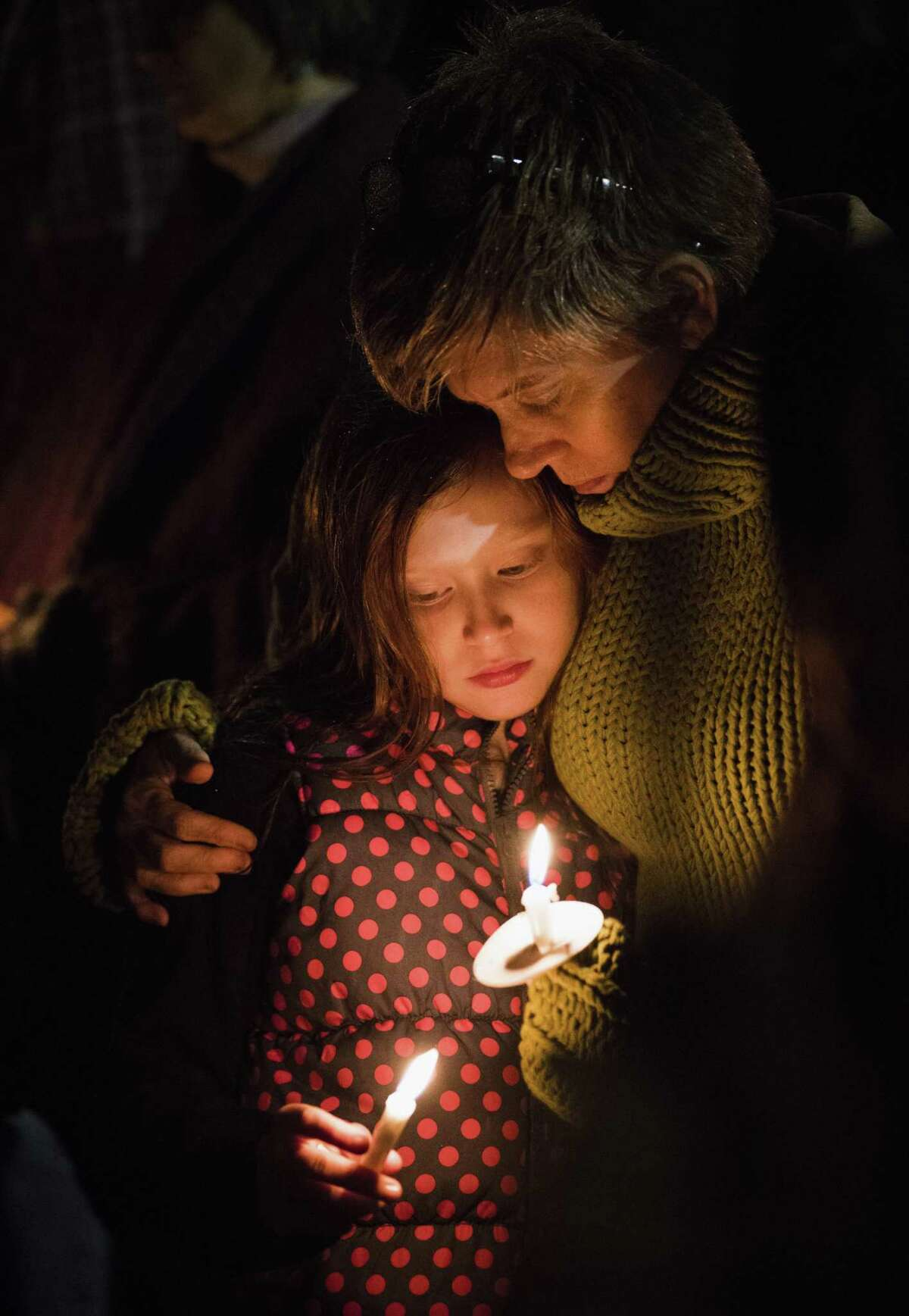 Ruby Lewis, 11, and mother Jennifer Khoshbin attend a candlelight vigil against gun violence held Wednesday at Madison Square Presbyterian Church in San Antonio. Midway through the event, the names of the 26 who died in Sutherland Springs were slowly read.