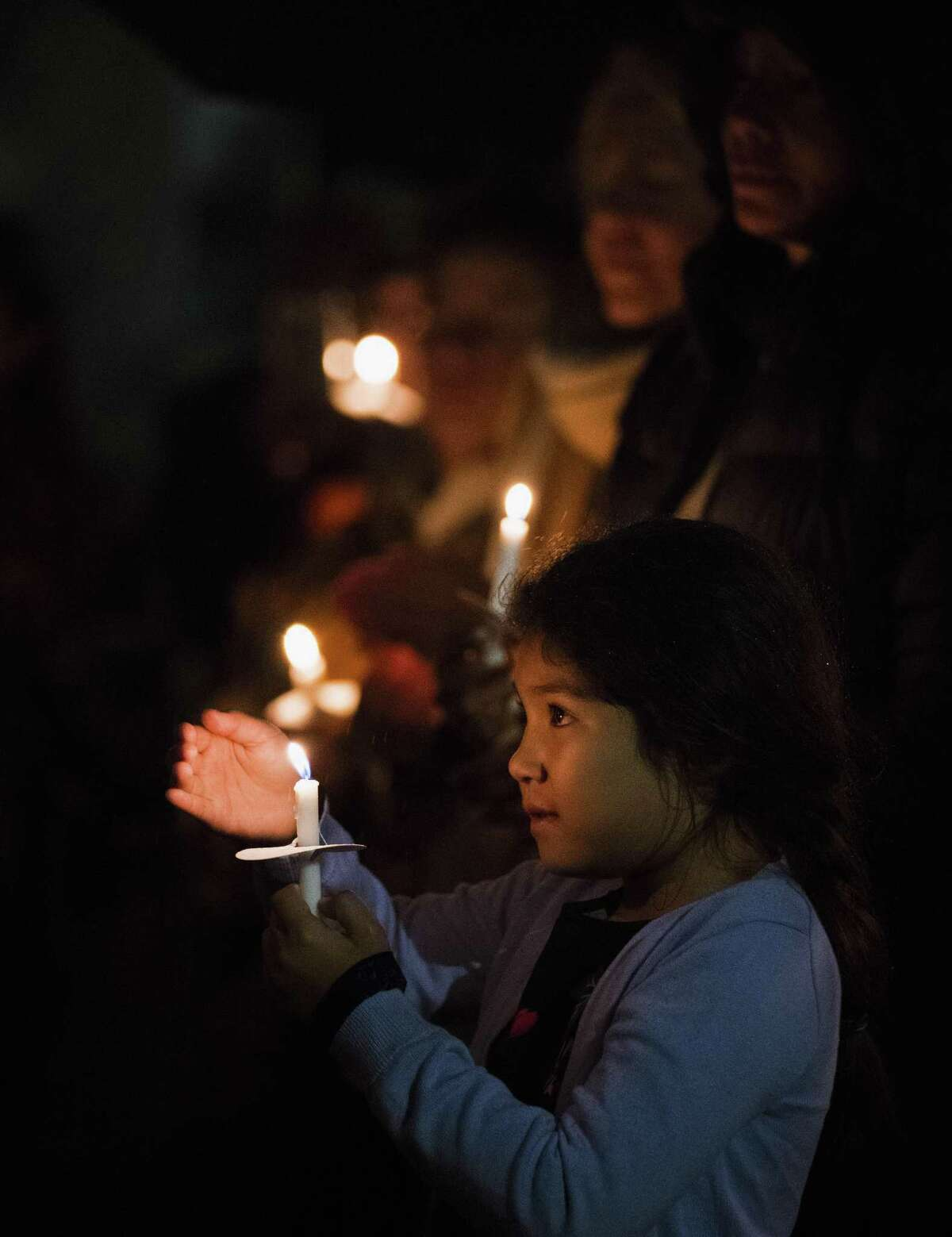 Seven-year-old Alexis holds a candle during a vigil against gun violence Wednesday in downtown San Antonio. The interfaith vigil was held for the 26 churchgoers shot to death Sunday in Sutherland Springs.