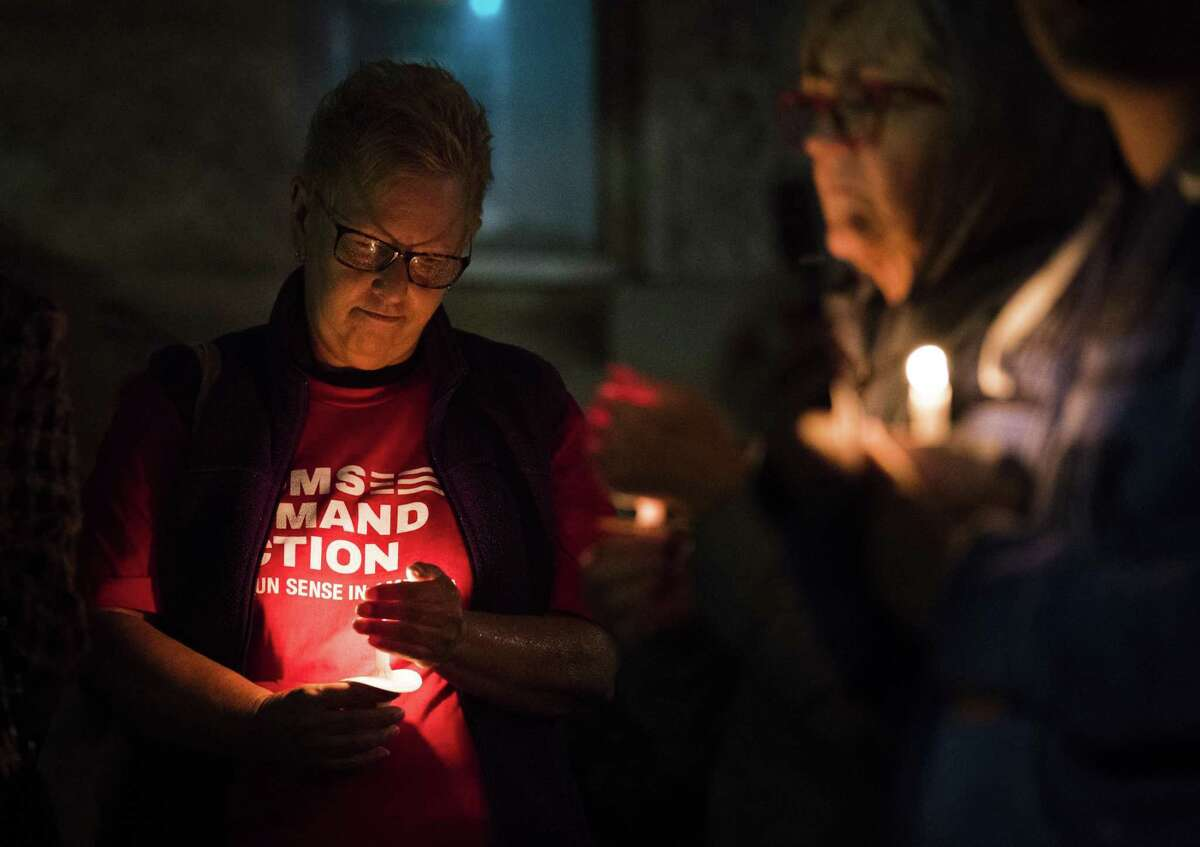 """Cat Yuracka (left) holds a candle during a vigil against gun violence Wednesday at Madison Square Presbyterian Church. The vigil was hosted by the San Antonio branch of of """"Moms Demand Action for Gun Sense in America,"""" a movement patterned after Mothers Against Drunk Driving."""