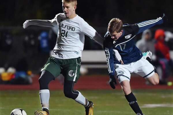 Guilford junior forward Eric LePeak moves in to score battling Wethersfield sophomore midfielder Riley Carlson and scores in the second half of the match in the second round of the Class L boys state soccer tournament, Wednesday, Nov. 8, 2017, at the Kavanaugh Complex at Guilford High School. Guilford won, 4-2.