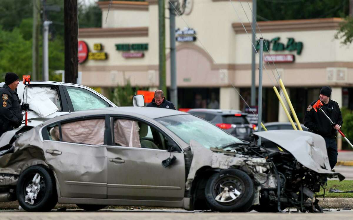 Harris County Sheriff's Office deputies investigate the scene of a two-vehicle crash on the intersection of Barker Cypress Road and FM 529 Thursday, Nov. 9, 2017, in Houston. One person was killed in the crash.