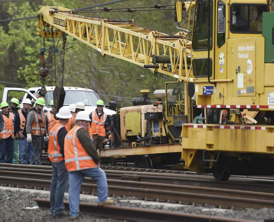 MTA employees gather after a piece of construction equipment derailed between in Greenwich, Conn. on May 5, 2016, resulting in a minor injury to one worker. Photo: Tyler Sizemore / Hearst Connecticut Media / Greenwich Time