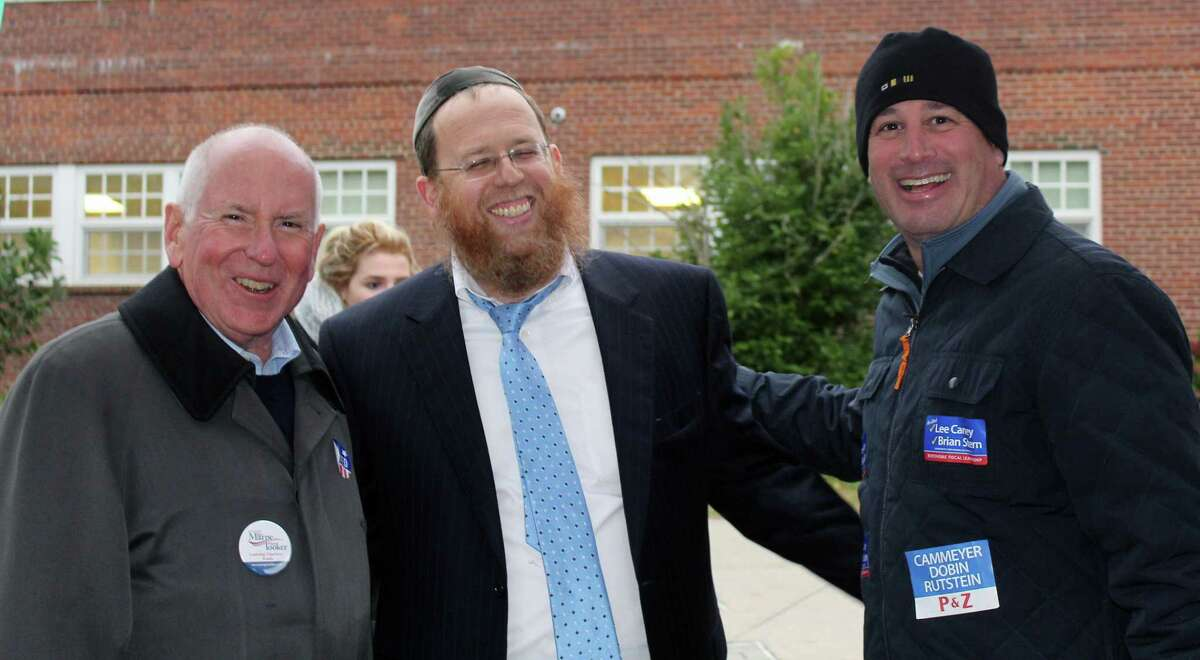 Newly re-elected First Selectman Jim Marpe, R, gathers outside of the Saugatuck Elementary School polling place on election day with Rabbi Yehuda Kantor and re-elected Board of Finance member Lee Caney, D.