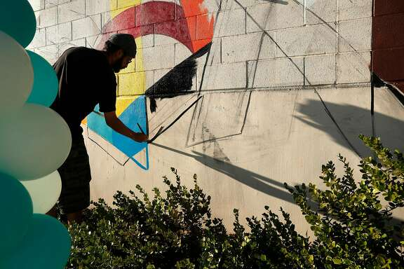 Muralist Max Martilla paints a mural on East Oakland Youth Development Center as before Covered California unveils it in Oakland, Calif., on Tuesday, November 7, 2017.