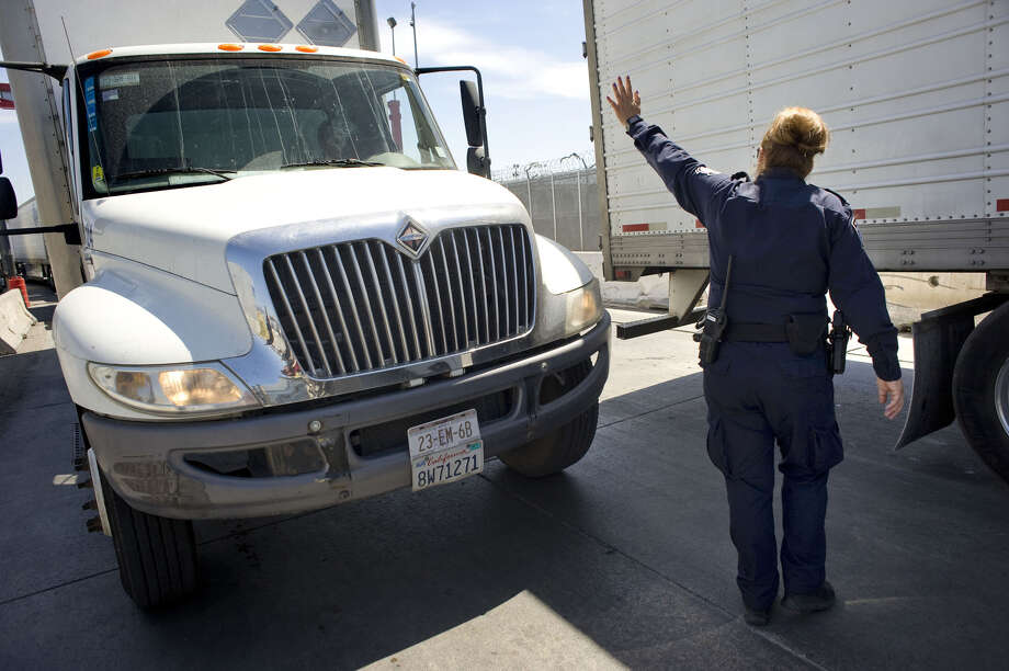 A U.S. Customs and Border Protection (CBP) officer signals to a truck entering from Mexico at A border crossing in San Diego. Photo: Bloomberg Photo By David Maung. / © 2017 Bloomberg Finance LP