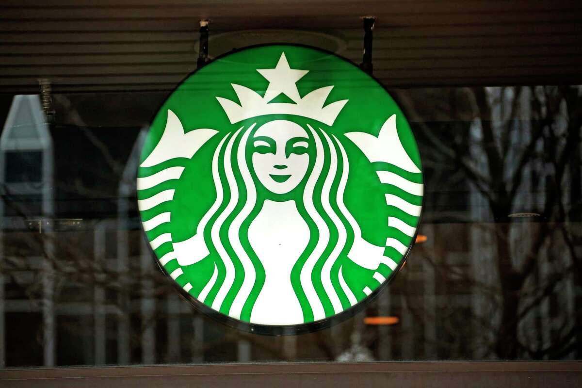 FILE - A Jan. 12, 2017 file photo shows a Starbucks logo sign in the window of one of the chain's cafes.