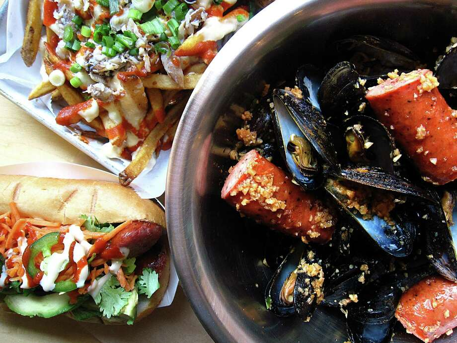 Clockwise from top left: Loaded Pinch Fries, mussels with sausage and a Banh Dog sandwich from Pinch Boil House and Bia Bar. Photo: Mike Sutter /San Antonio Express-News