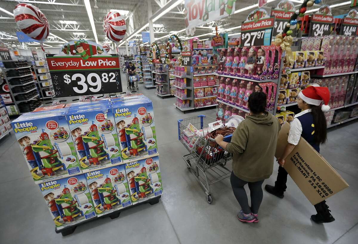 FILE - In this Wednesday, Oct. 26, 2016, file photo, a shopper, left, walks with a store associate in the toy section at Walmart in Teterboro, N.J. Walmart hopes to tempt shoppers with online deals before Black Friday. It's beginning some online deals Thursday and plans to offer most of its Black Friday deals online starting at 12:01 a.m. on Thanksgiving. (AP Photo/Julio Cortez, File)