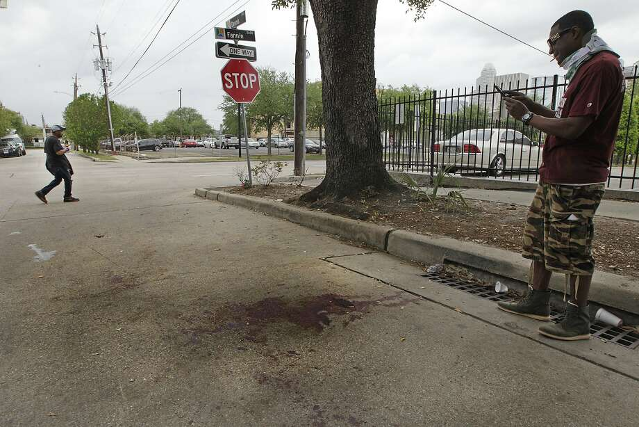 Ariel Johnson photographs the blood stains on Dennis Street where a double homicide happen Monday, April 11, 2016, in Houston's Midtown. Police were called Dennis Street in the early-morning hours Monday and found two men shot and beaten. (Steve Gonzales  / Houston Chronicle  ) Photo: Steve Gonzales, Houston Chronicle