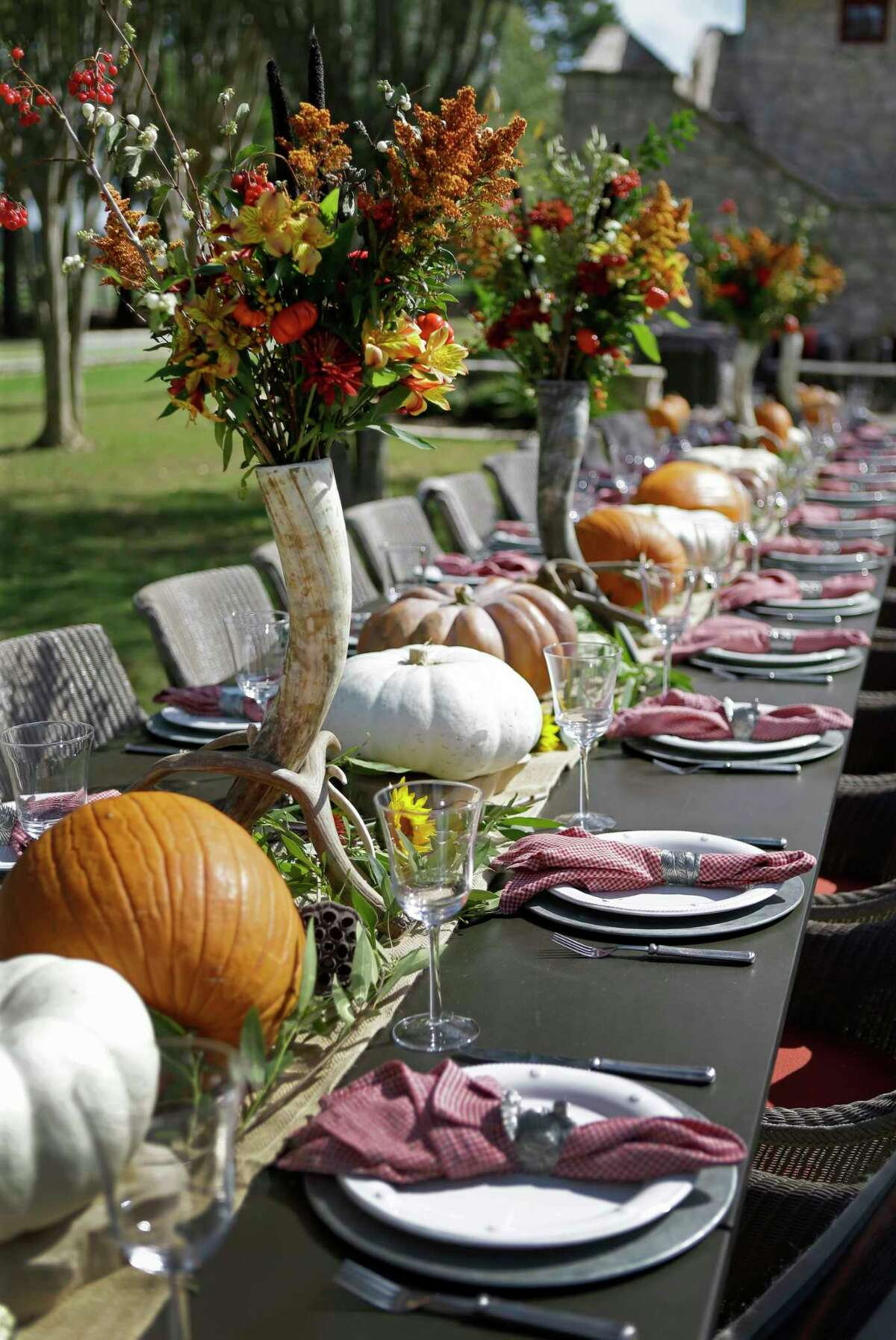 Lucas-Eilers Design Associates designed an outdoor tablescape for 28 using pumpkins, gourds, antlers and tall, skinny vases holding a bouquets of fall colors above the crowd. Tableware courtesy of Kuhl-Linscomb.