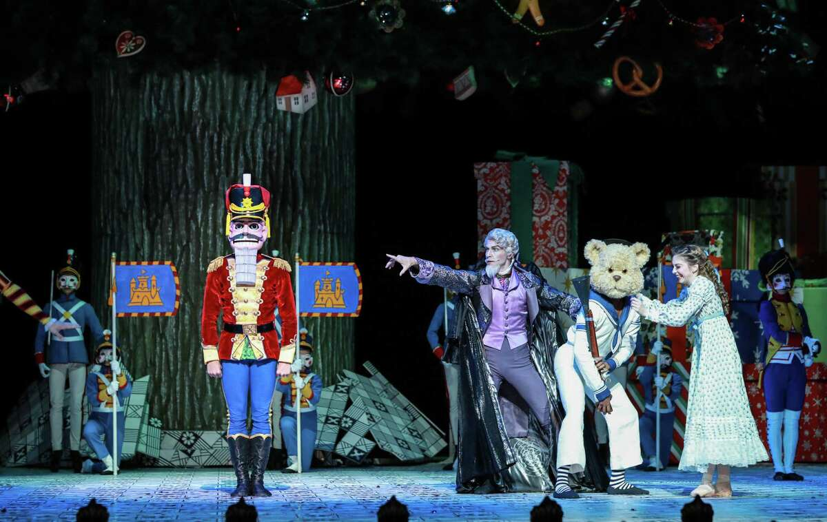 """Drosselmeyer (Ian Casady, center) introduces a Nutcracker doll to Clara (Melody Mennite, far right) in Act I of Stanton Welch's new staging of """"The Nutcracker"""" for Houston Ballet."""