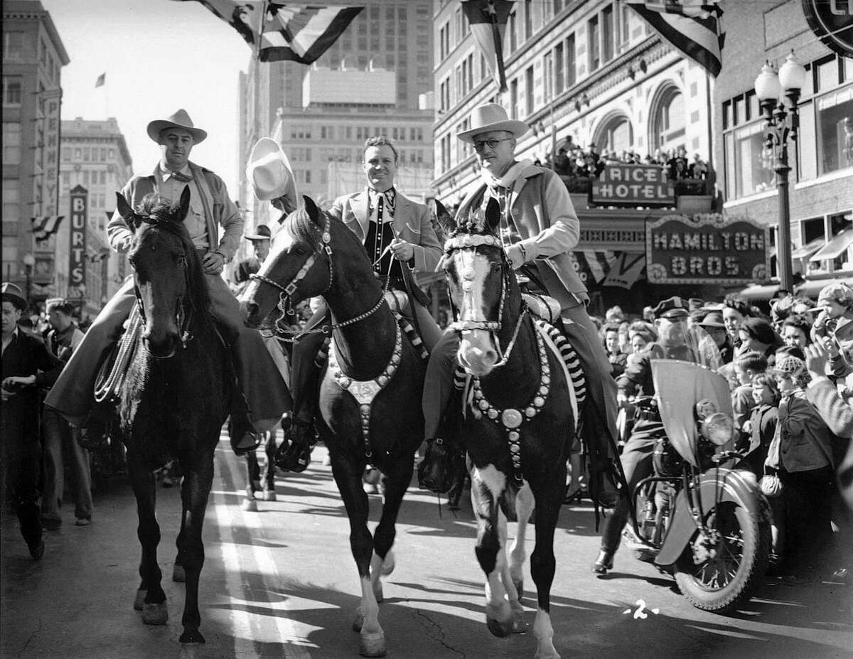Signage on the Rice Hotel advertising Hamilton Shirts is seen behind this 1942 photo of western movie star Gene Autry on his horse, Champion, as he leads the Houston Fat Stock Show & Rodeo on Main Street in downtown Houston.
