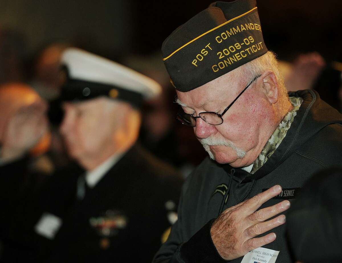 Stratford veteran Dick Kennedy bows his head during the singing of the National Anthem during the Veterans Day Celebration ceremony at Bunnell High School in Stratford, Conn. on Thursday, November 9, 2017.