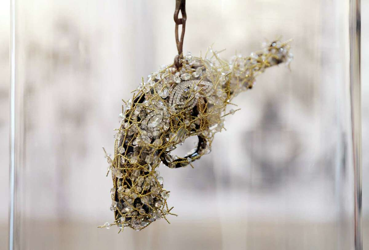 Artist Karin Broker with a crystal jeweled toy gun piece under glass at her home studio.