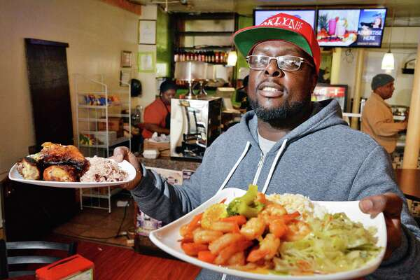 Mekeo, a co-owner of Irie Vybez restaurant in Albany, holds orders of jerk chicken and butter shrimp. (John Carl D'Annibale/Times Union)