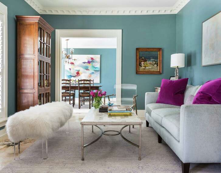 This seating area includes cool blues with a pop of bright pink in sofa pillows. The interior designer is Cheryl Baker of CDB Interiors.
