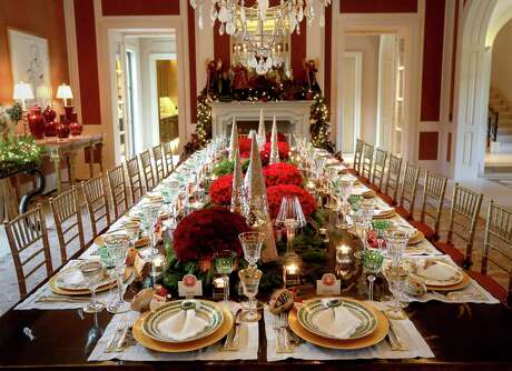 Sheridan and John Eddie Williams have lavish and lovely tablescapes for formal holiday dinners. Their centerpieces include fresh red roses, glass Christmas trees, greenery and lots of candles.
