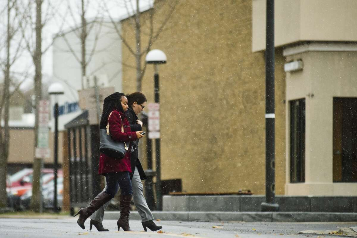 People cross McDonald Street as snowflakes begin to fall in downtown Midland on Thursday, Nov. 9, 2017. (Katy Kildee/kkildee@mdn.net)