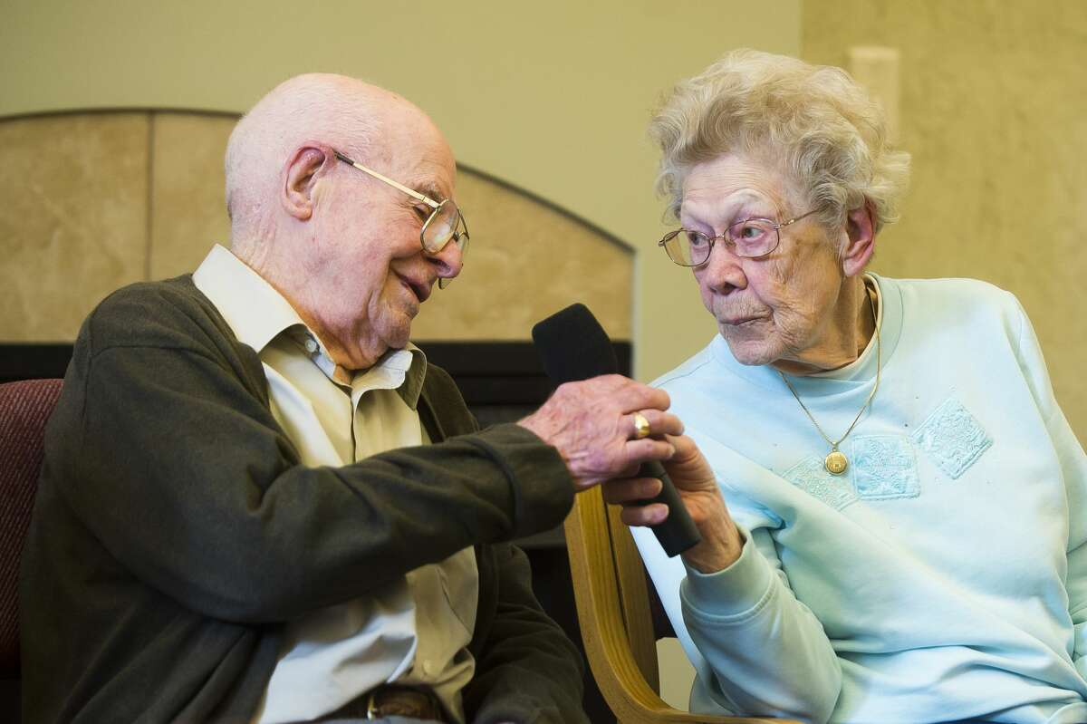 Frieda Milano, 100, right, passes a microphone to Howard Shaver, 100, during a conversation between a panel of four Midland centenarians on Thursday, Nov. 9, 2017 at the Herbert D. Doan Midland County History Center. (Katy Kildee/kkildee@mdn.net)