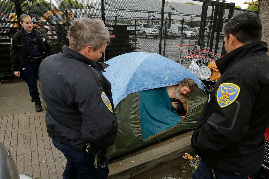 Members of the San Francisco Police Department's Homeless Outreach Unit visit a camp on Folsom Street near 18th Street in June and talk with Army veteran John Hunter. Photo: Michael Macor, The Chronicle