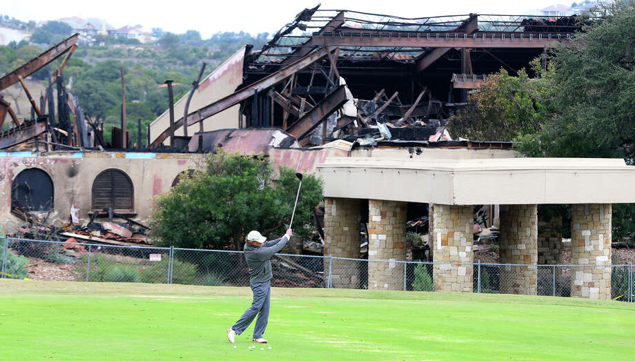 A man golfs in front of the burned club house at the Tapatio Springs Hill Country resort near Boerne, Texas. A fire destroyed the building Saturday night November 4, 2017. Tapatio Springs is on 220 acres in the Hill Country. Its 18-hole golf course recently underwent a $2 million renovation. One of its owners is country music star George Strait. Photo: John Davenport/San Antonio Express-News
