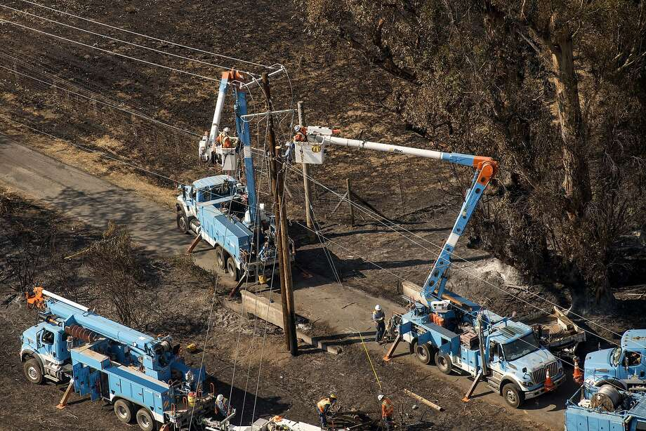 Pacific Gas & Electric Co. (PG&E) employees work to fix downed power lines burned by wildfires in this aerial photograph taken above Santa Rosa, California,on Oct. 12, 2017. MUST CREDIT: Bloomberg photo by David Paul Morris. Photo: David Paul Morris, Bloomberg