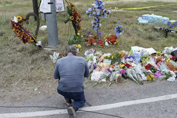 A man prays by a memorial for the First Baptist Church victims in Sutherland Springs. Gun control deniers, with help from congressional allies, are keeping any debate from occurring.