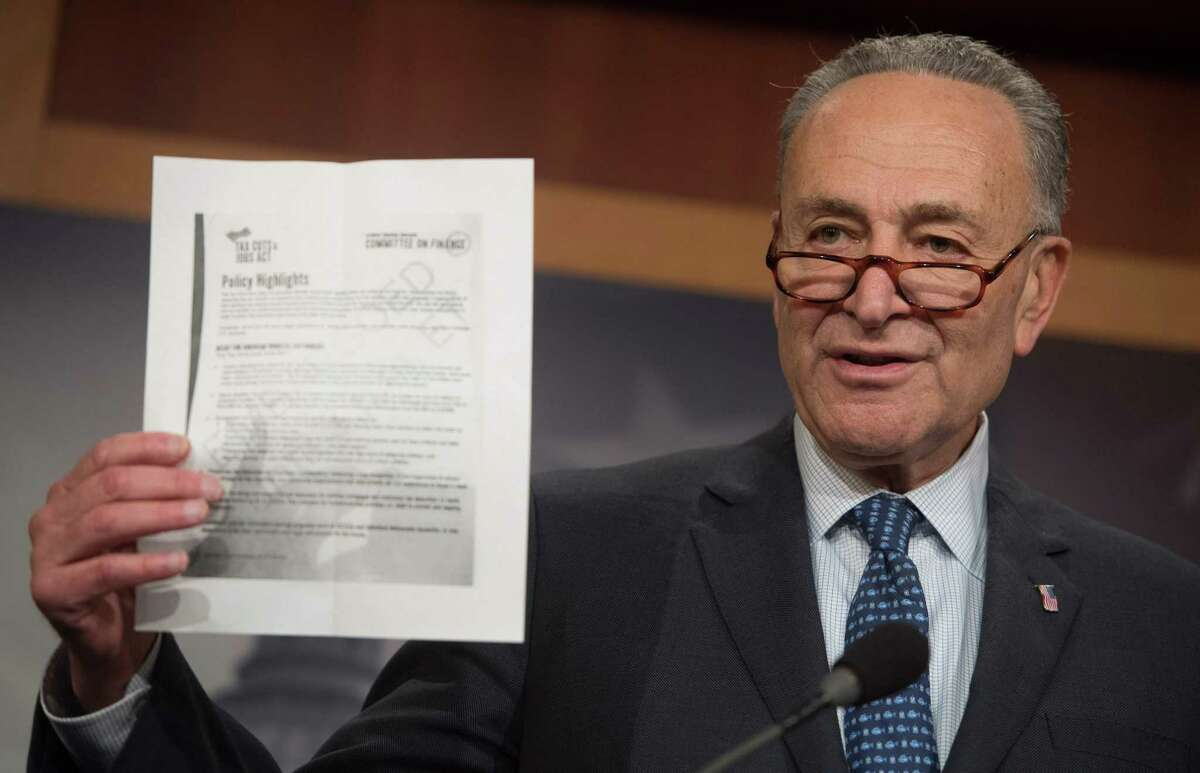 US Senate Minority Leader Chuck Schumer, Democrat of New York, holds up talking points from the Republican Senate tax reform bill during a press conference on Capitol Hill in Washington, DC, November 9, 2017.