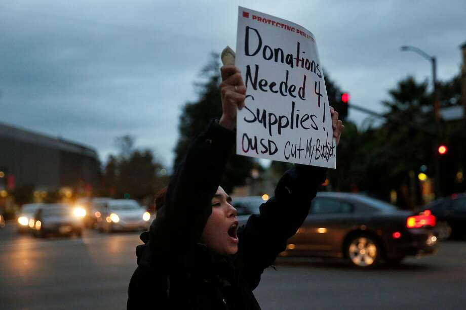 Teacher Roxana Miles grips a sign and a donation she got for supplies at a protest against budget cuts for Oakland schools. Photo: Leah Millis, The Chronicle