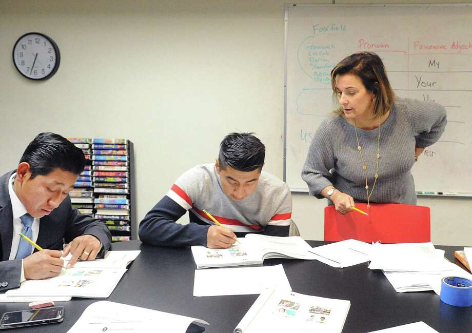 Judy Betz, a Family Centers English language volunteer tutor, right, teaches English while students Xavier Morocho, center, and Juan Ordonez, left, both Greenwich residents, take part at BANC in Greenwich on Wednesday. Photo: Bob Luckey Jr. / Hearst Connecticut Media / Greenwich Time