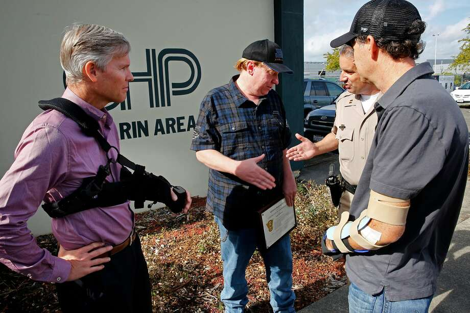 Two of the four bicycle riders struck by the vehicle, Joe Olla, (left)  and Spencer Fast, (right) along with CHP Captain Robert Mota, greet James McPherson at the Marin office of the CHP after a commendation was given to McPherson on Thursday Nov. 9, 2017, in Corte Madera, Calif. McPherson was honored by the CHP for providing helmet video of a pickup truck hitting four bicyclists back on Oct. 7th. Photo: Michael Macor, The Chronicle