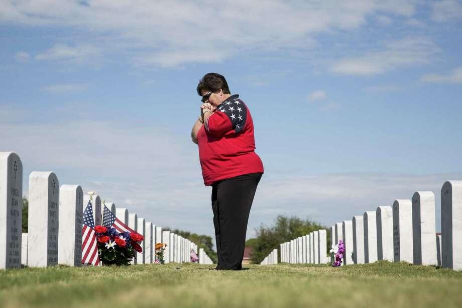 Judy Carlile visits her Vietnam veteran husband's grave  in 2016. Photo: San Antonio Express-News /File Photo / 2016 San Antonio Express-News