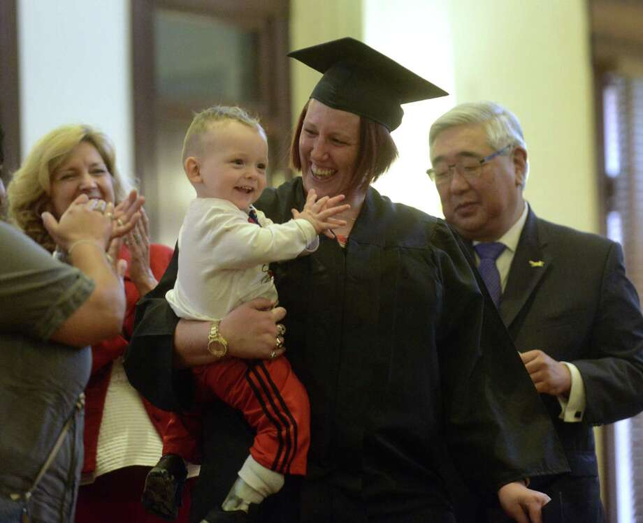 Brandi Dishner holds her son, Codi, during the graduation ceremony of the second class of the Bexar County Early Intervention Program at the Bexar County Courthouse on Nov. 9, 2017. The parents were reunited with children after completing requirements stipulated by Child Protective Services and the court. Photo: Billy Calzada /San Antonio Express-News