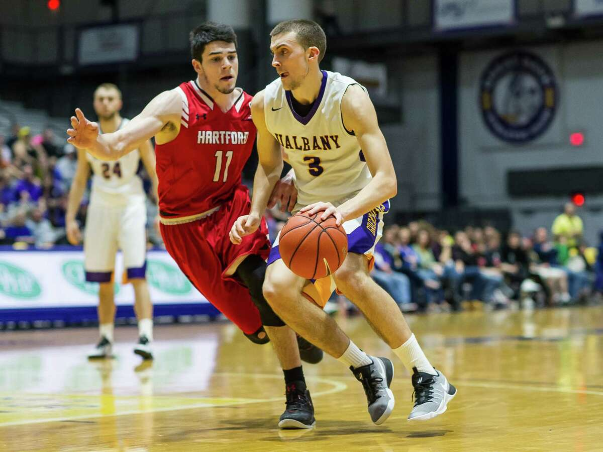 UAlbany's Joe Cremo takes the ball to the basket against Hartford's Andrew Rameriz during Saturday's game. (Bill Ziskin / UAlbany Athletics)