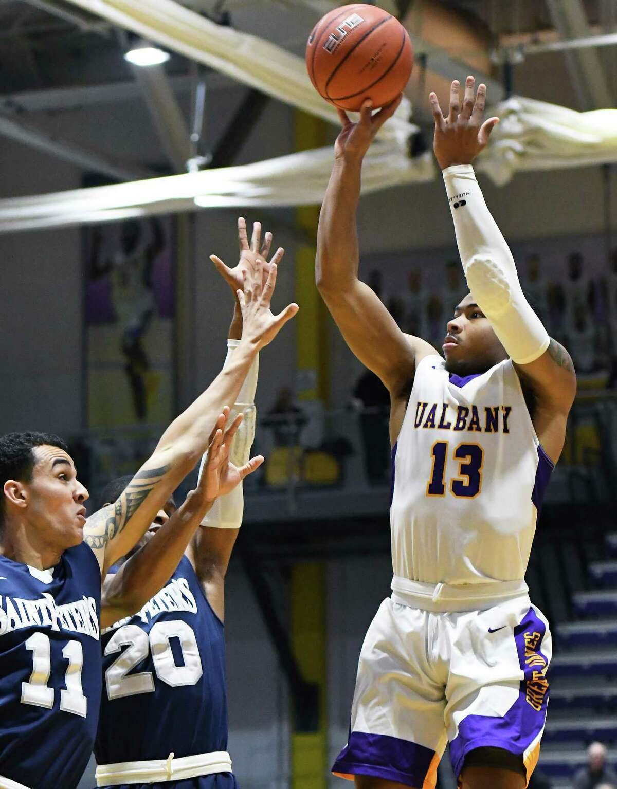 UAlbany's #13 David Nichols, right, gets a shot past Saint Peter's defenders #20 Chazz Patterson and #11 Nnamdi Enechionyia, left, during their CIT Tournament game Thursday March 16, 2017 in Albany, NY. (John Carl D'Annibale / Times Union) ORG XMIT: MER2017031621410085