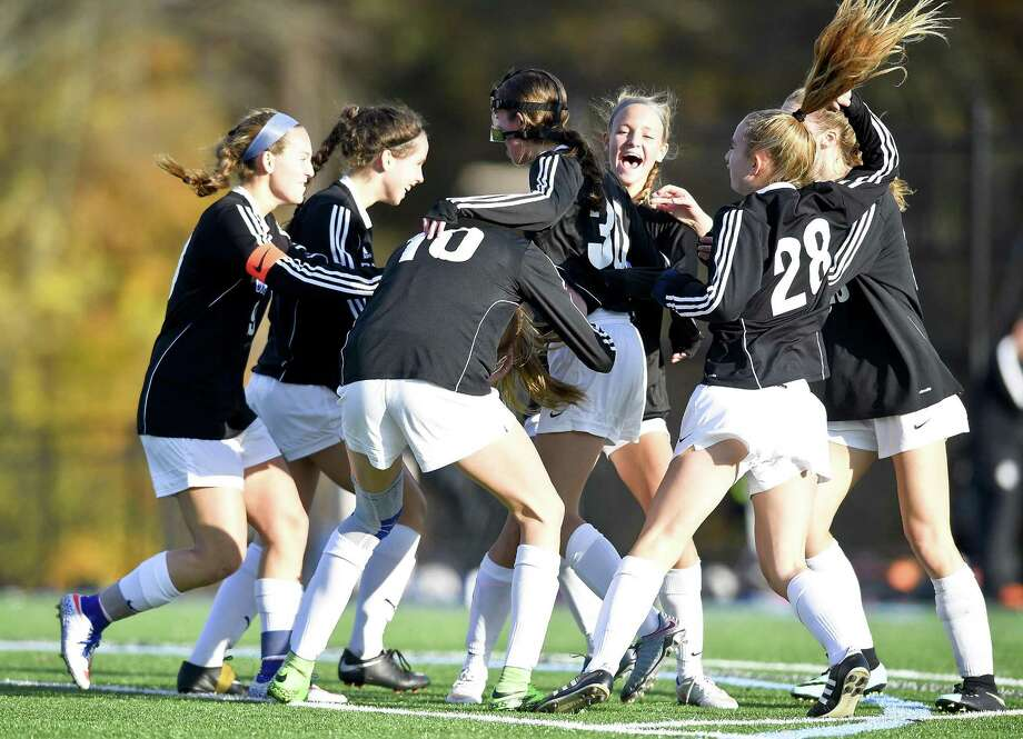 Darien's Onora Brown (30) is mob by her teammates as they celebrate her game wining goal against Shelton in the second half during a Class LL Second Round game in the CIAC 2017 State Girls Soccer Tournament at Darien High School in Darein, Connecticut on Thursday, Nov. 9, 2017. Darien defeated Shelton 2-1. Photo: Matthew Brown / Hearst Connecticut Media / Stamford Advocate
