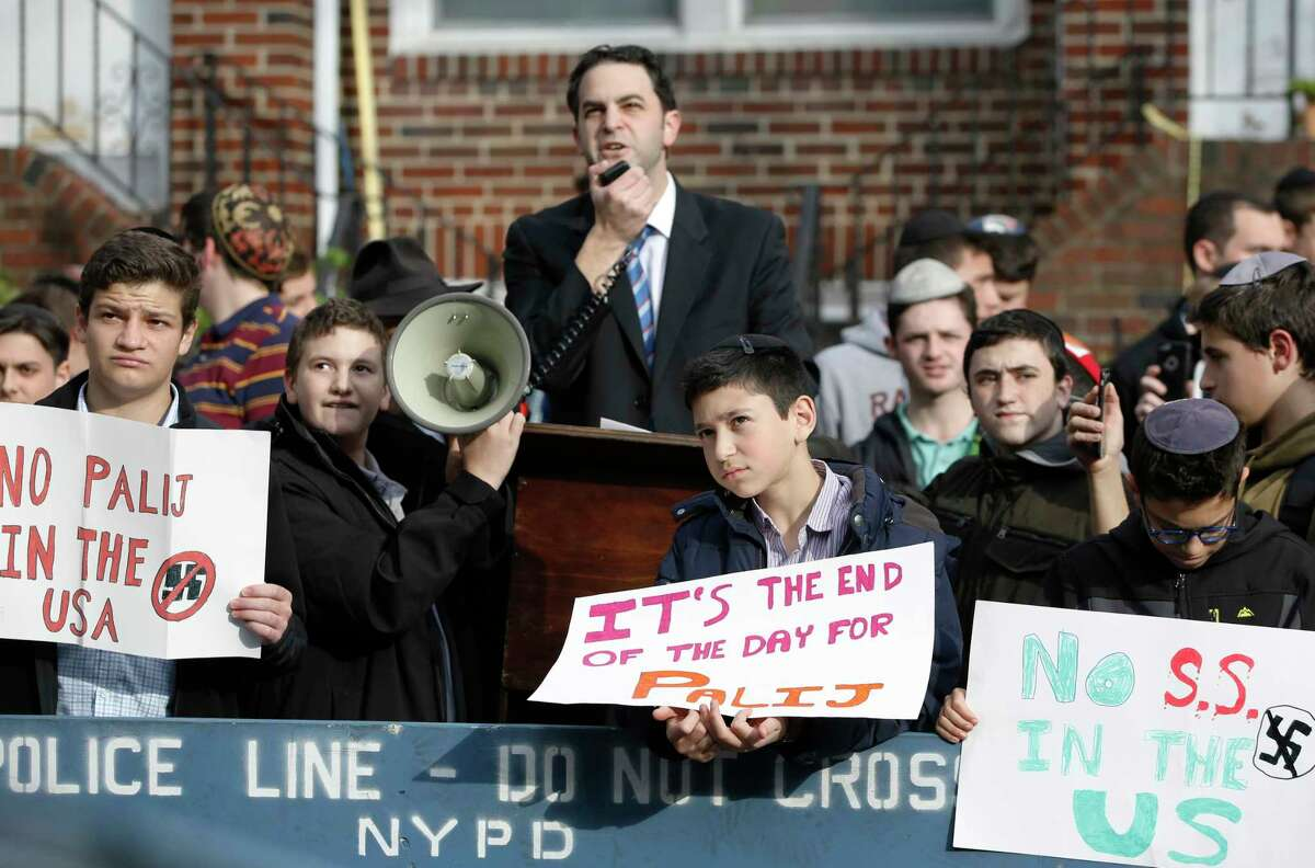 Hillel Goldman, associate principal of the Orthodox Jewish Rambam Mesivta High School, speaks as he and students from the school protest across the street from the house of former Nazi concentration camp guard Jakiw Palij, 94, who worked as a guard at the Nazi German Trawniki SS camp in occupied Poland in 1943, Thursday, Nov. 9, 2017, in the Jackson Heights neighborhood of New York. About a hundred students from the school joined the protest to oust the Nazi war criminal from the United States on the 79th anniversary of Kristallnacht. (AP Photo/Kathy Willens) ORG XMIT: NYKW103