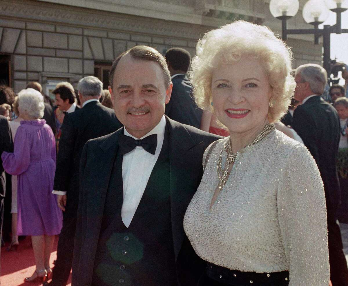 FILE- This Sept. 22, 1985, file photo shows John Hillerman, left, and Betty White, right, arriving at Emmy Awards in Pasadena, Calif. A spokeswoman for the family of Hillerman says the co-star of TV?'s ?