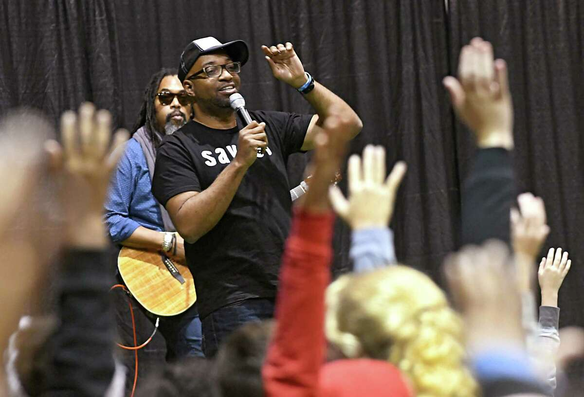 Author and poet Kwame Alexander holds a literary pep rally with Schenectady City School District students at the Schenectady Armory on Thursday, Nov. 9, 2017 in Schenectady, N.Y. Musician Randy Preston plays guitar and sings behind him. (Lori Van Buren / Times Union)