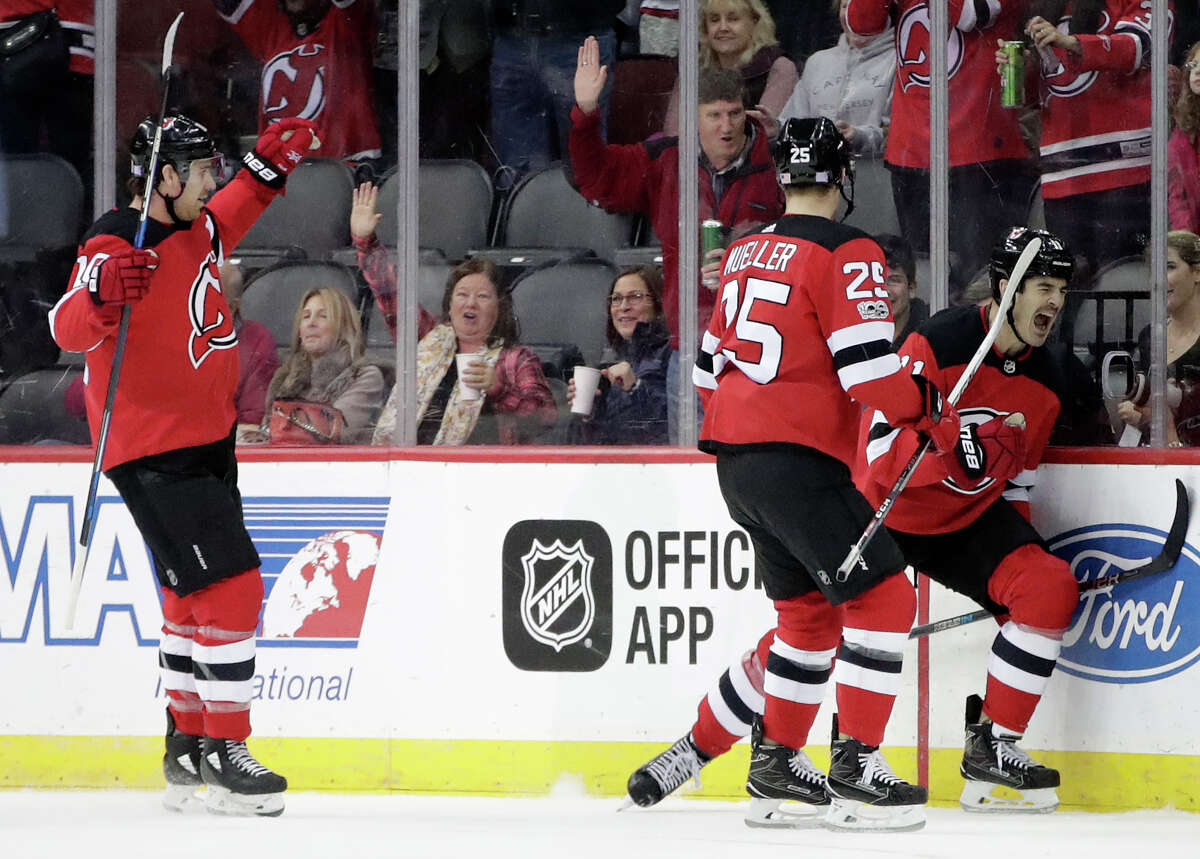 New Jersey Devils center Brian Boyle, right, celebrates his first-period goal with teammates Mirco Mueller(25), of Switzerland, and Jimmy Hayes (10) during an NHL hockey game against the Edmonton Oilers, Thursday, Nov. 9, 2017, in Newark, N.J. (AP Photo/Julio Cortez)